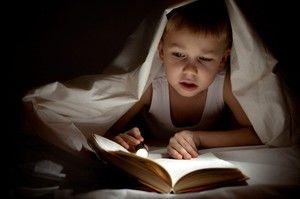 Otrok bere knjigo v slabi luči
